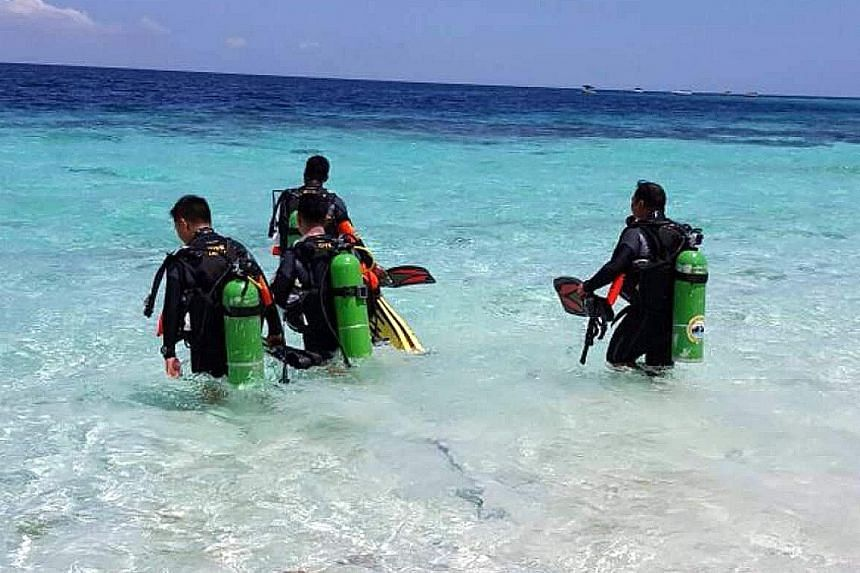 """Malaysia has tasked its first four dive marshals (pictured) to act as """"undersea policemen"""" to prevent divers from damaging the coral around Sipadan Island, which is located off Sabah. The waters around Sipadan are popular with divers around the world"""