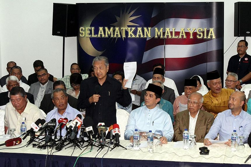 """Tan Sri Muhyiddin Yassin (front row, second from left) and Datuk Seri Mukhriz Mahathir (front row, far right) at the """"citizens' declaration"""" press conference organised by former PM Mahathir Mohamad (standing) last Friday in Kuala Lumpur."""