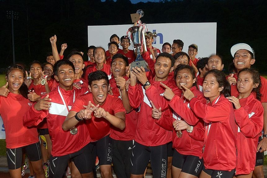 (Above) Athletes from the Singapore Sports School celebrating yesterday after being crowned overall champions of the SPH Schools Relay Championships for the sixth consecutive year. (Right) Prem Sathiamoorthy, from the triumphant Raffles Institution 4