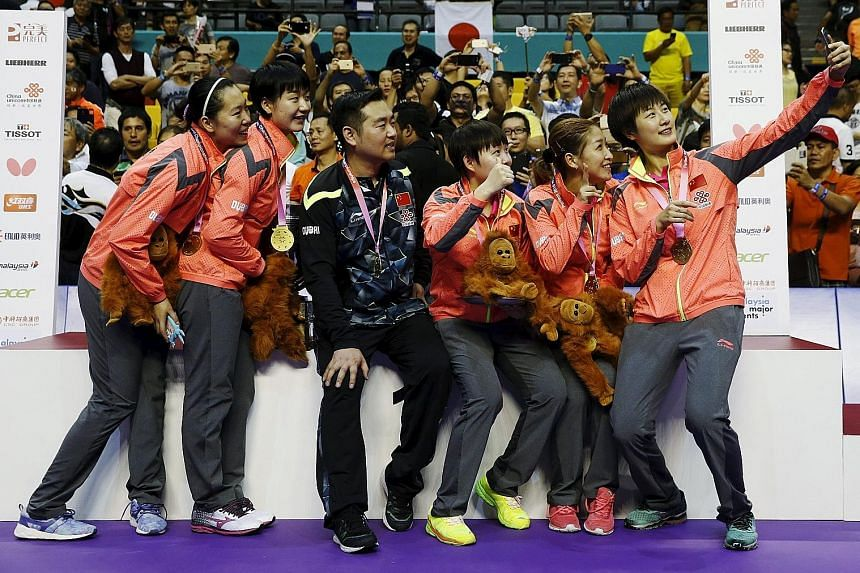 The Chinese women's team, with coach Kong Linghui, posing for a wefie with their winners' medals after their 11th crown in 12 championships.