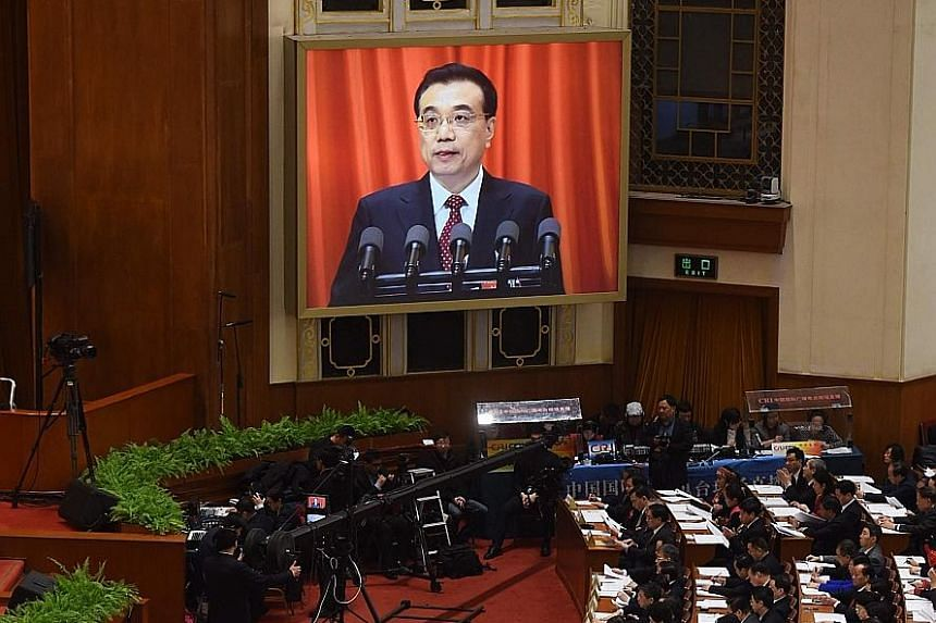 Mr Li seen on a screen during the National People's Congress opening session on Saturday. He unveiled a 6.5 to 7 per cent growth goal, down from 7 per cent last year.