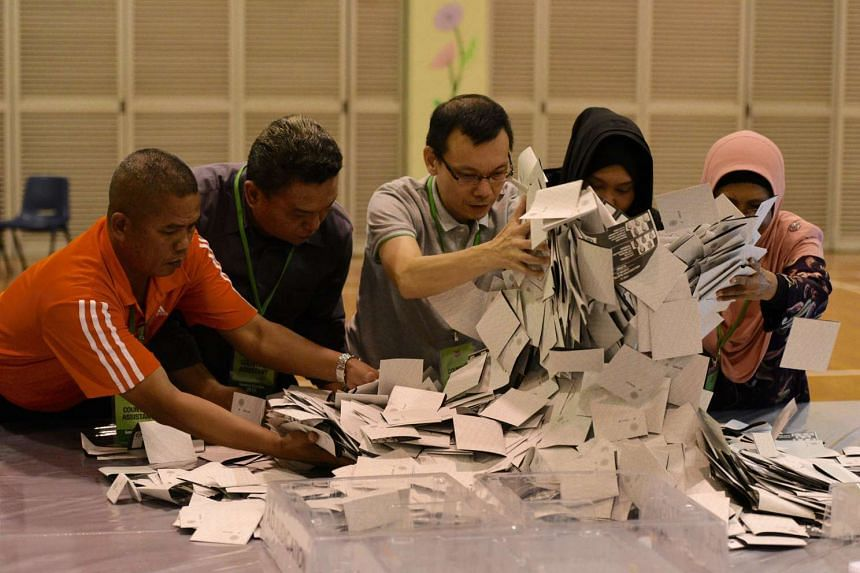 Counting assistants pouring out ballot papers for counting at Bedok Town Secondary School on Sept 11, 2015.