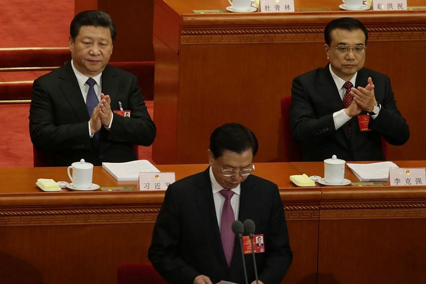 Chinese President Xi Jinping (left) and Chinese Premier Li Keqiang clap while Zhang Dejiang (centre), chairman of the Standing Committee of the National People's Congress prepares to speak at the 12th National People's Congress (NPC) in Beijing, Chin