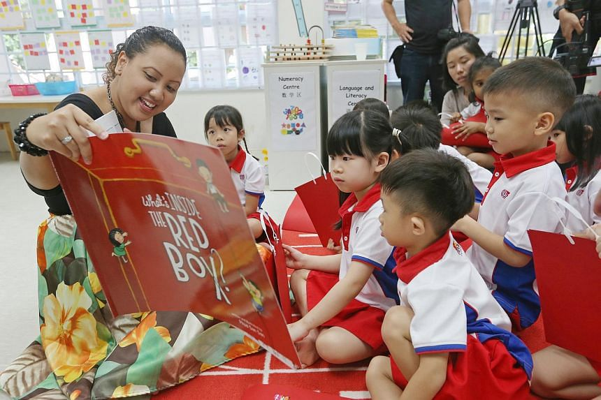 Preschool teacher Suhartina Buang reading What's Inside The Red Box to the pupils at PCF Sparkletots in Radin Mas.