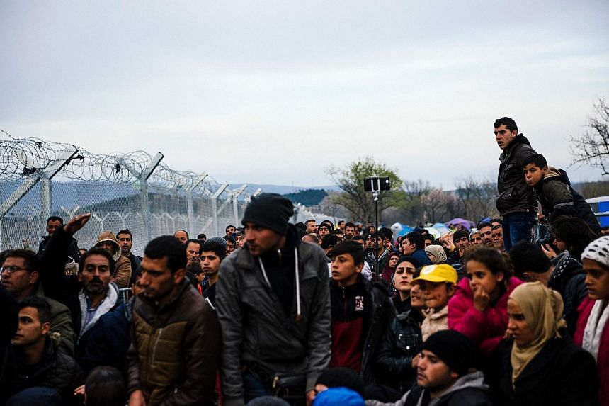 People gather near the gate at the Greek-Macedonian border, on March 6, 2016.