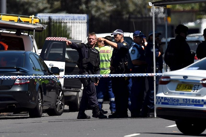 Police and emergency services personnel are behind a road block at the scene of a shooting in the western Sydney suburb of Ingleburn, on March 7, 2016.
