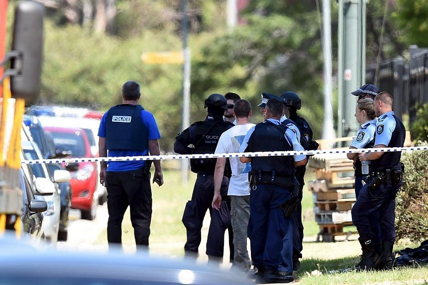Police officers are seen behind a road block at the scene of a shooting in the western Sydney suburb of Ingleburn, Australia, on March 7, 2016.