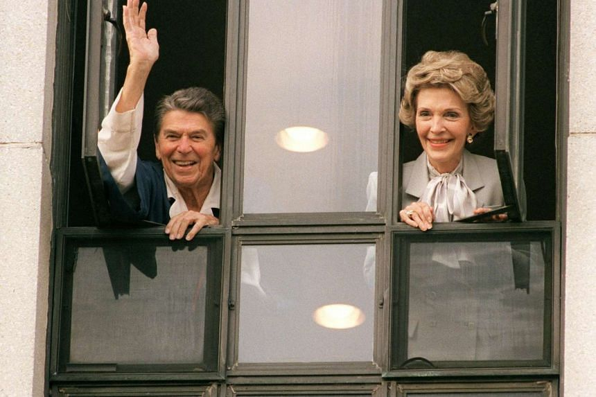 Then-US President Ronald Reagan waves to the press from the window of his room at Bethesda Naval Hospital with First Lady Nancy Reagan on Jan 6, 1987.
