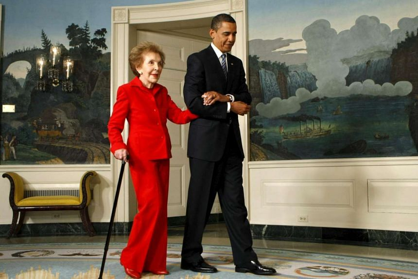 US President Barack Obama escorts former first lady Nancy Reagan to a signing ceremony for the Ronald Reagan Centennial Commission Act at the White House on June 2, 2009.