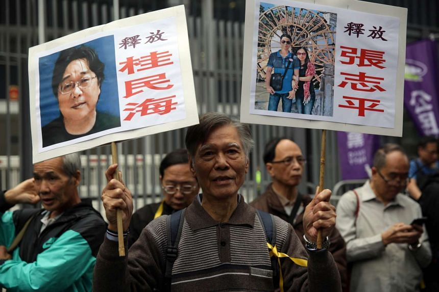 A protester in Hong Kong with placards showing some of the missing booksellers from the city's Mighty Current publishing house, a publisher known for books critical of Beijing.