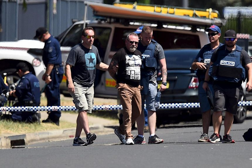 Police leading a handcuffed man away from the scene of a shooting in the western Sydney suburb of Ingleburn, Australia, on March 7, 2016.