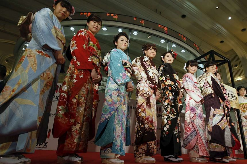 Women pose for pictures at the Tokyo Stock Exchange.