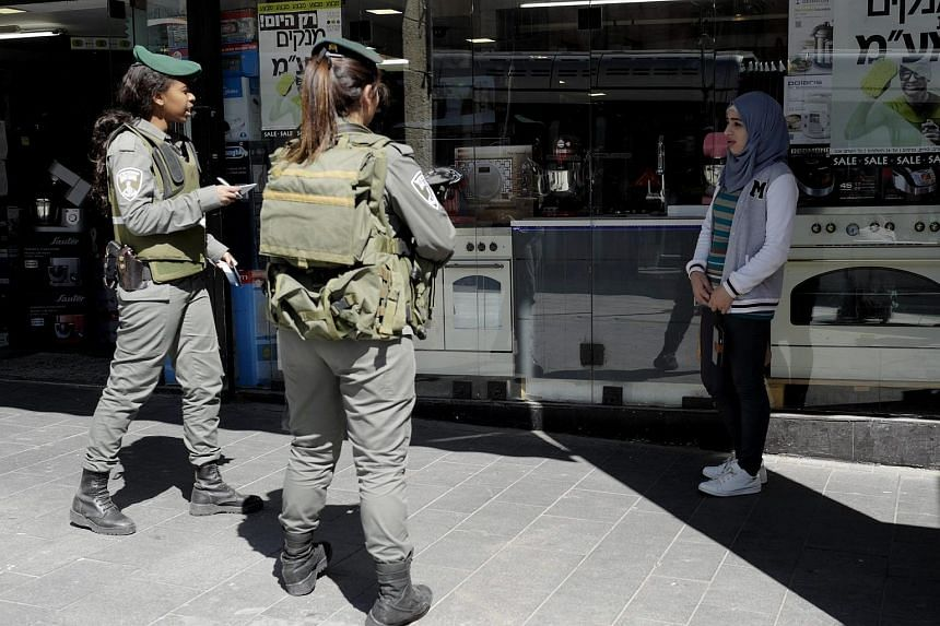 Israeli Border Policewomen stop a teenage Arab girl and carry out an identity check in Jerusalem on Feb 24, 2016.