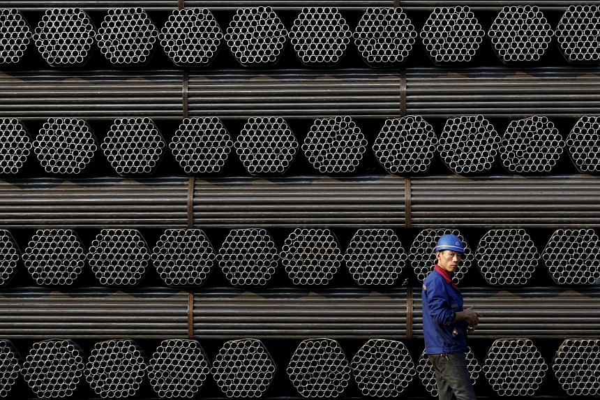 A worker walking past a pile of steel pipe products in China's Hebei province on Nov 3, 2015.