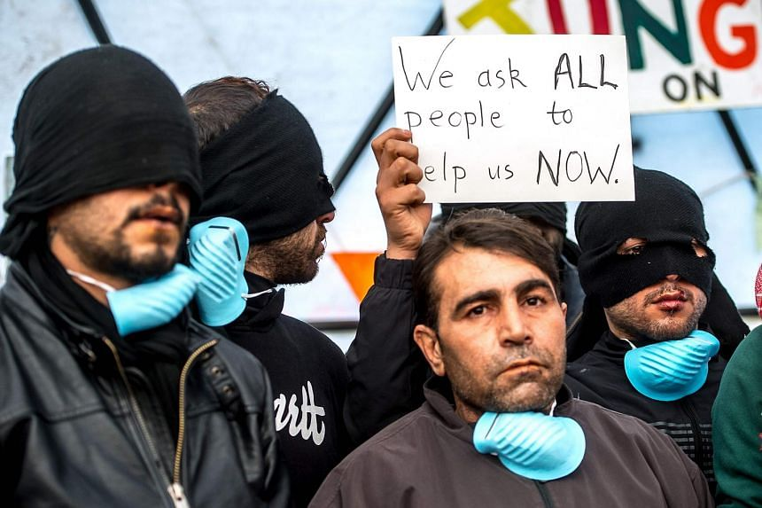 """Iranian migrants with their lips sewn shut hold signs at the """"Jungle"""" migrant camp on March 4, 2016."""
