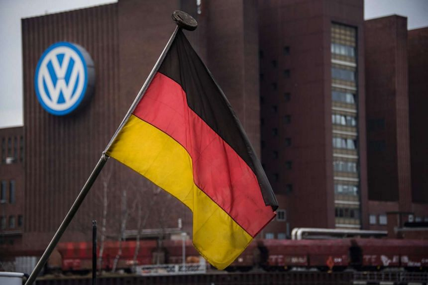 A German flag with the Volkswagen HQ plant in the background in Wolfsburg, Germany, on March 7, 2016.