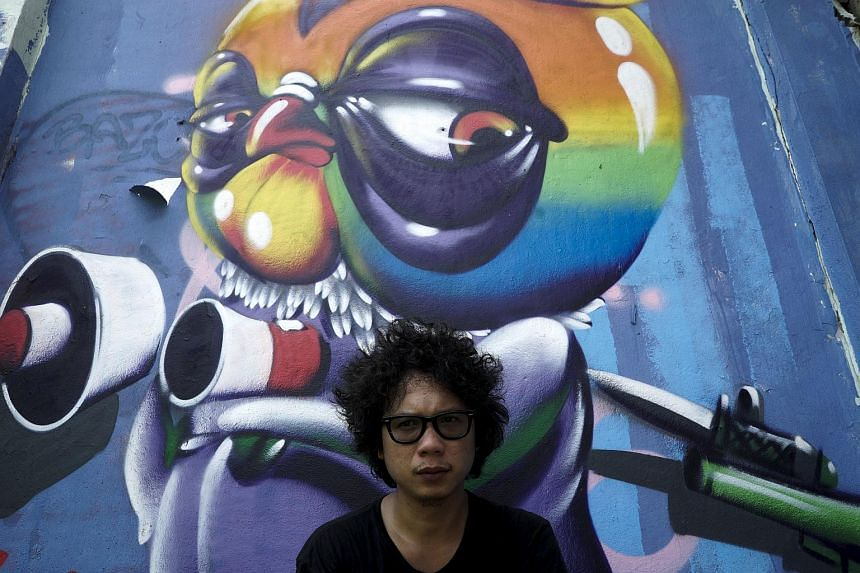 Asin Acid poses near his graffiti in Bangkok, Thailand on March 7, 2016.