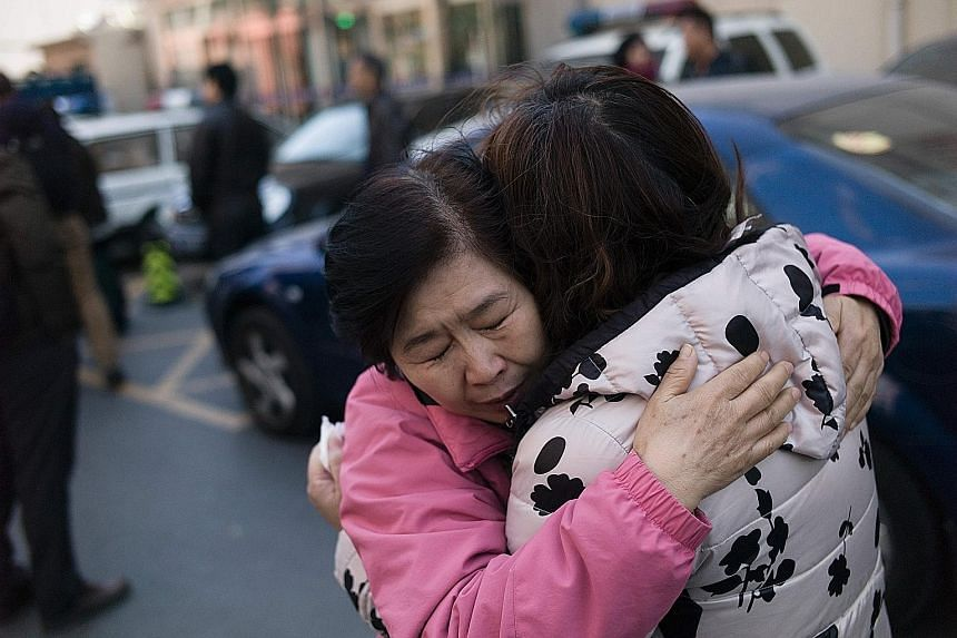 Relatives of Chinese passengers aboard missing Flight MH370 comforting each other yesterday outside the Beijing Rail Transportation Court, which has been designated to handle MH370 cases. The plane, with 239 people on board, including 153 Chinese cit