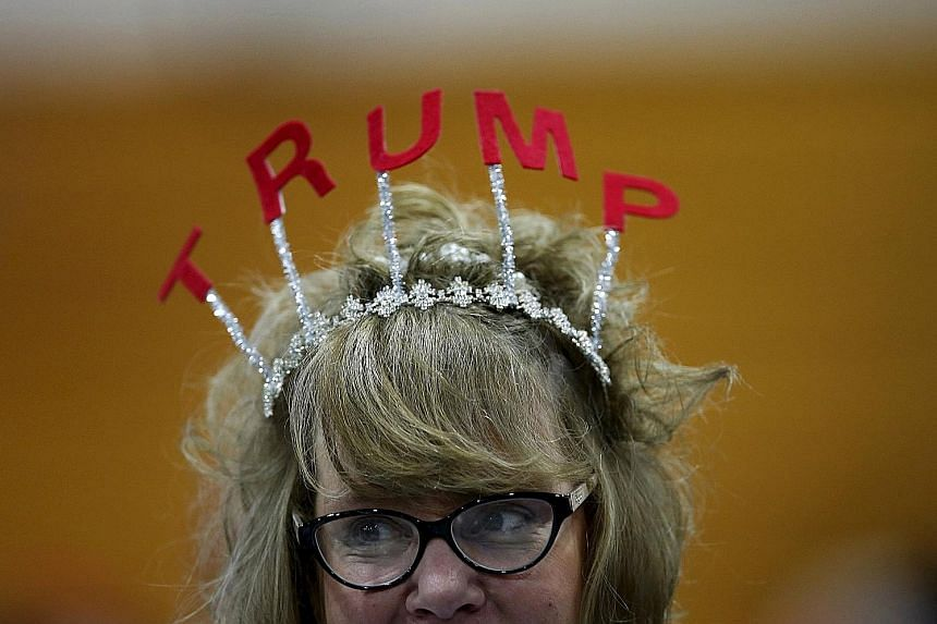 Voters (left, from top) showing their support for US Republican presidential candidate Donald Trump - with headgear and a shoe signed by him - at campaign rallies in the Michigan cities of Cadillac and Warren last Friday. Mr Trump has a polling lead