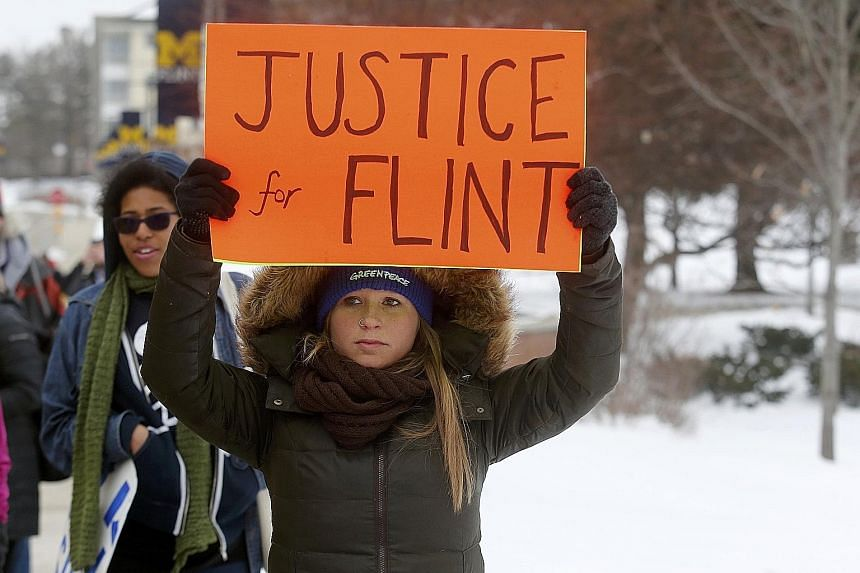 A volunteer distributing bottled water in Flint, Michigan. The city's water was tainted after its supply was switched under Republican governor Rick Snyder. Demonstrators (left) protesting against the crisis on Sunday.