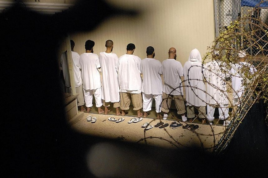 A group of detainees performing their morning prayers in Camp Delta, Guantanamo Bay Naval Base, in this photo taken in 2009. The problem for each detainee is that the US government has to find a place that is willing to take him, and that can be trus