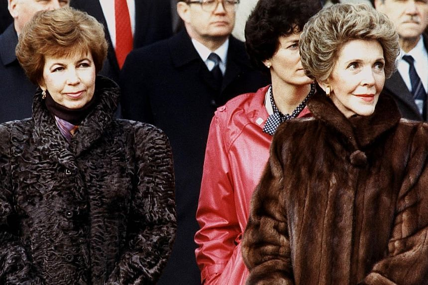 Mrs Reagan (left) at a ceremony to receive the Congressional Gold Medal in 2002; (top) with Mr Ronald Reagan in a 1952 engagement photo; and with Mrs Raisa Gorbachev (above, left) at the White House in 1987.