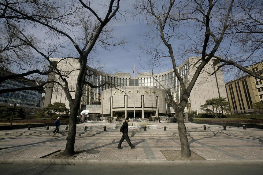 People walk past the headquarters of the central bank of the People's Republic of China in Beijing, on Feb 16, 2009.