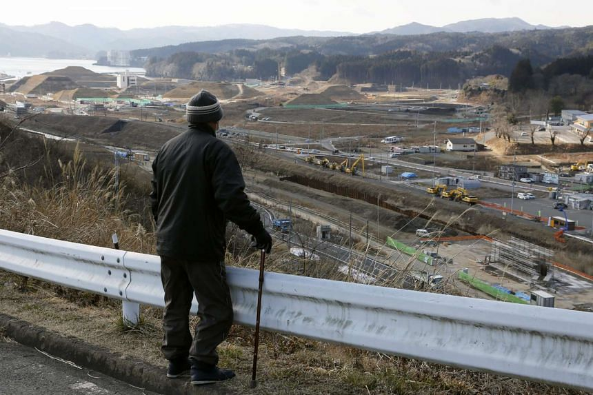 A local resident looks out across recovery work going on in Shizugawa town in Minamisanriku, in northern Japan's Miyagi prefecture, on Feb 27, 2016.