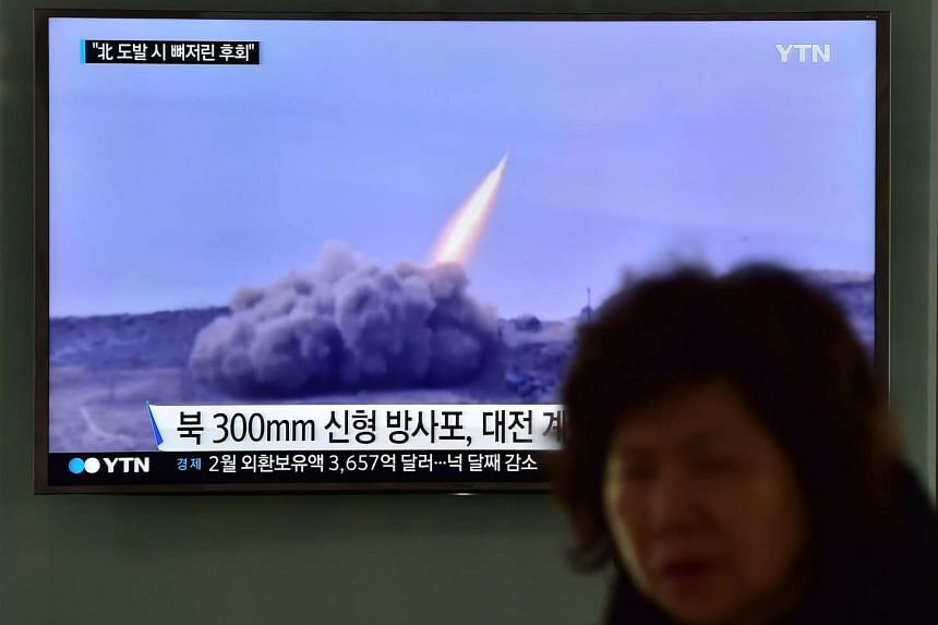 A woman walks past a television screen showing a news broadcast on North Korea's latest missile launch, in Seoul on March 4, 2016.