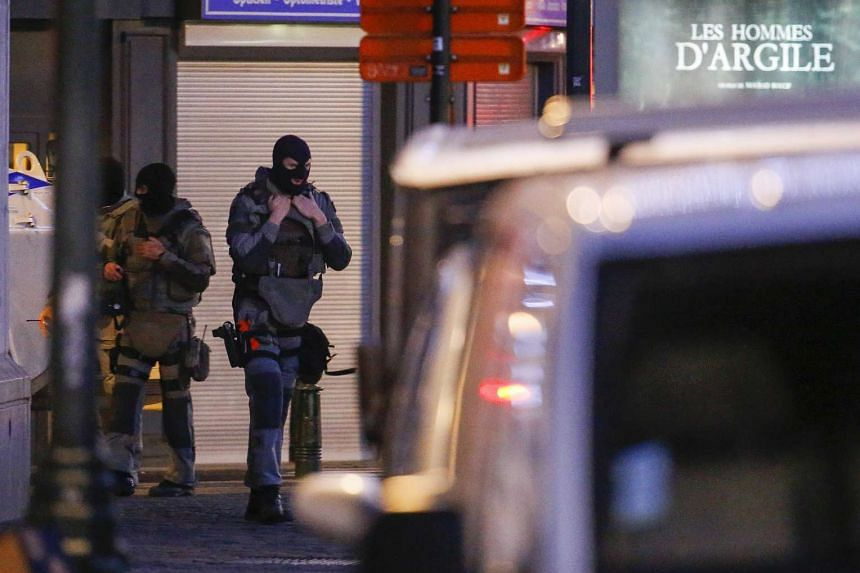 Belgian special forces police officers patrol a street during a police raid in central Brussels, Belgium in December in connection with the deadly Paris attacks.