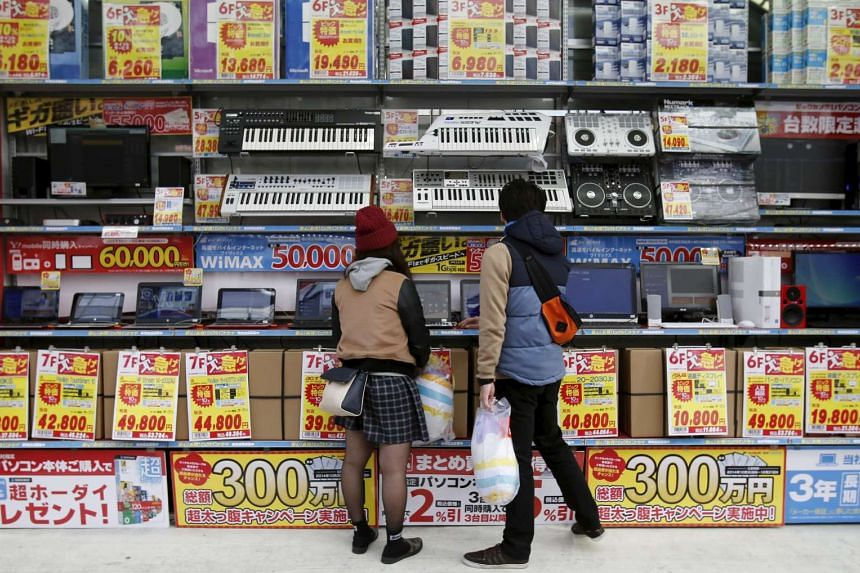 People try out laptops displayed at an electronics retail store in Tokyo, on Nov, 16, 2014.