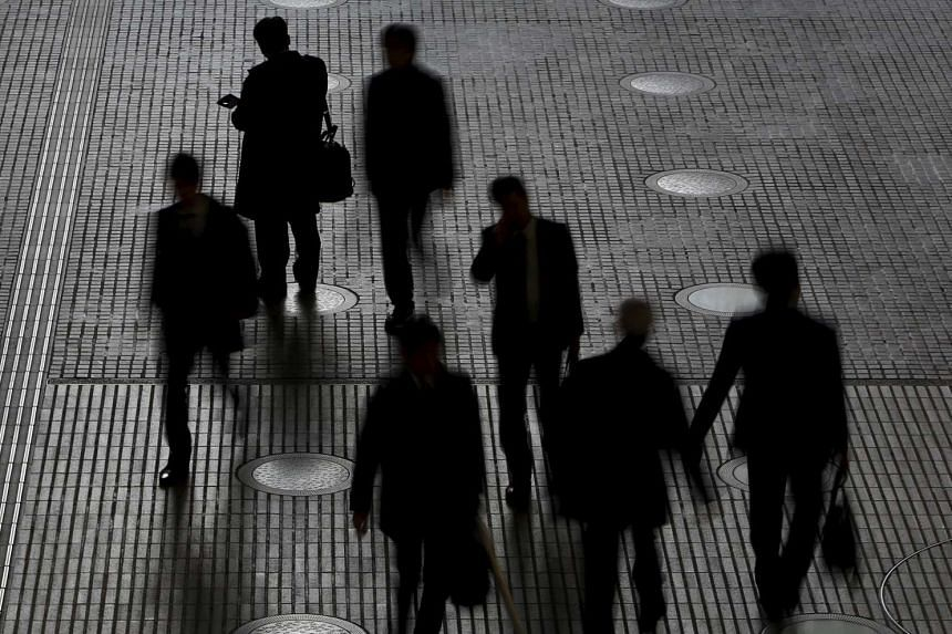 People walk at an office building at a business district in Tokyo, Japan, on Feb 29, 2016.