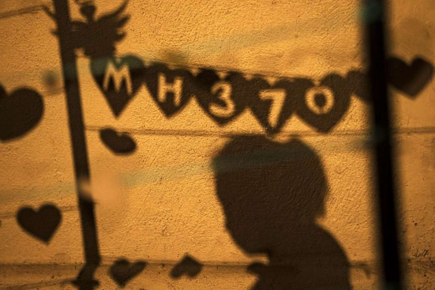 A woman's shadow and tributes to the passengers of flight MH370 are seen during an event in Kuala Lumpur on March 30, 2014.