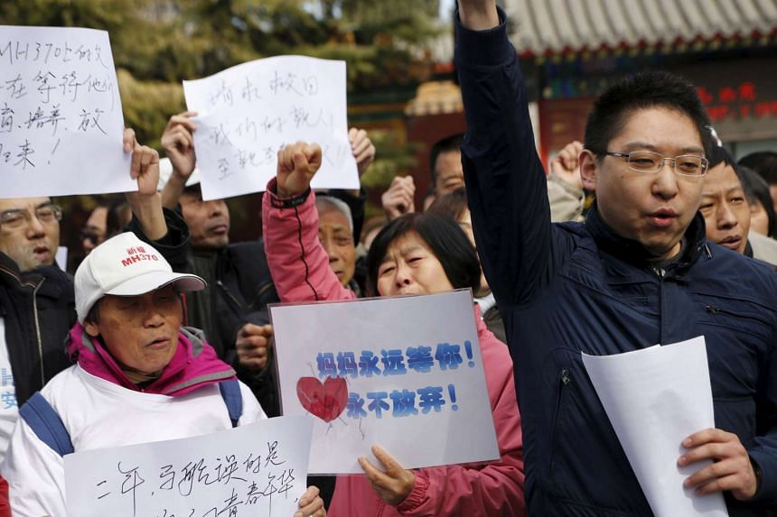 Family members of passengers onboard of Malaysia Airlines flight MH370  shout slogans at Lama Temple in Beijing, China, on March 8, 2016.