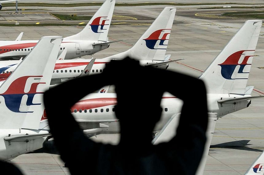 A man looks at Malaysia Airlines' aircraft parked on the tarmac at Kuala Lumpur International Airport in Sepang, on Feb 25, 2016.