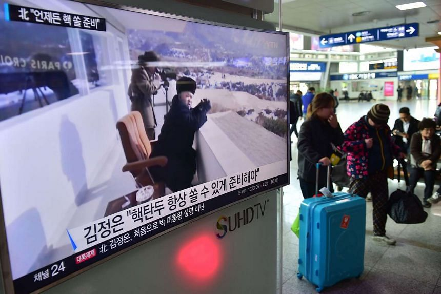 Travellers walk past a television screen showing file footage of North Korean leader Kim Jong Un, at a railway station in Seoul, on March 4, 2016.