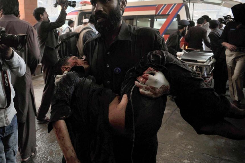 A Pakistani security officer moves a victim of the suicide bombing in Shabqadar to a hospital in Peshawar on Monday.