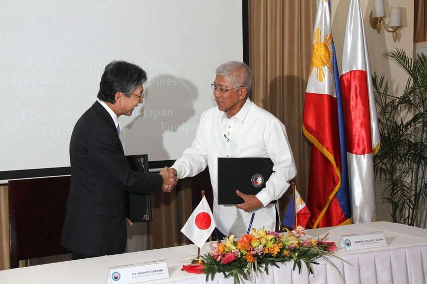 Filipino Defence Secretary Voltaire Gazmin (right) and Japanese Ambassador Kazuhide Ishikawa (left) shaking hands after signing an agreement on Feb 29, 2016.