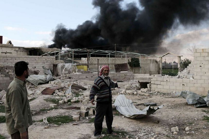 A Syrian man stands in the courtyard of his farm as smoke billows in the background following reported air strikes near the rebel-held village of al-Chifouniya, on the outskirts of the capital Damascus, on March 4, 2016.