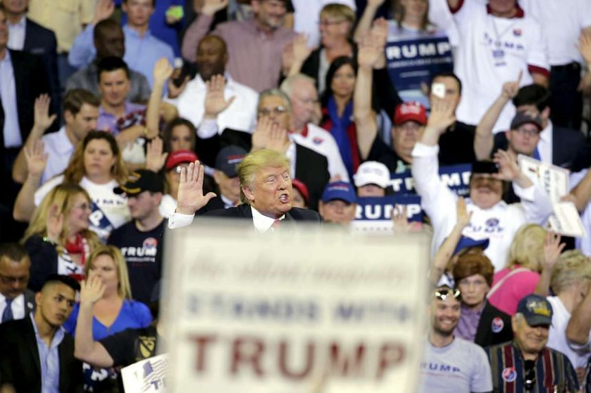 Republican US presidential candidate Donald Trump asks his supporters to raise their hands and promise to vote for him at his campaign rally at the University of Central Florida in Orlando, Florida on March 5, 2016.