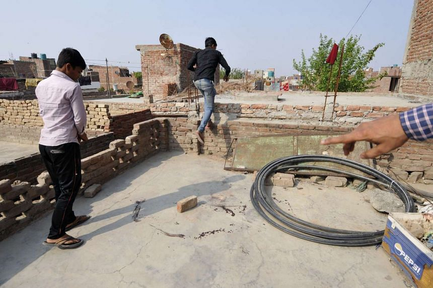 Indian youths point out the spot where a teenage girl was found after being allegedly raped and then set on fire in Greater Nioda, India, on March 8, 2016.
