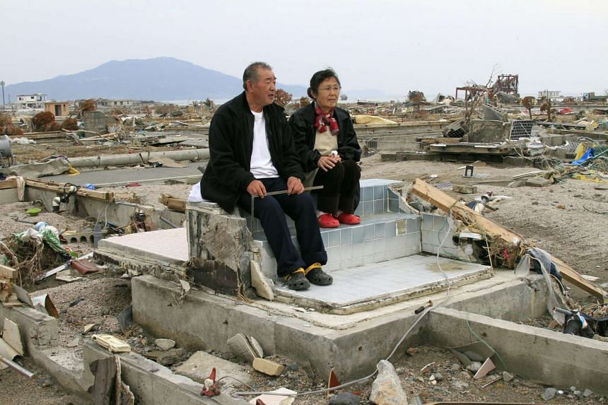 A file picture shows Mr Teizo Terasaka (left), 70, and his wife Keiko, 68, sitting on the remains of the bath tub of their house in tsunami-devastated city of Rikuzentakata, Iwate Prefecture, northern Japan, on May 1, 2011. March 11, 2016 marks the f