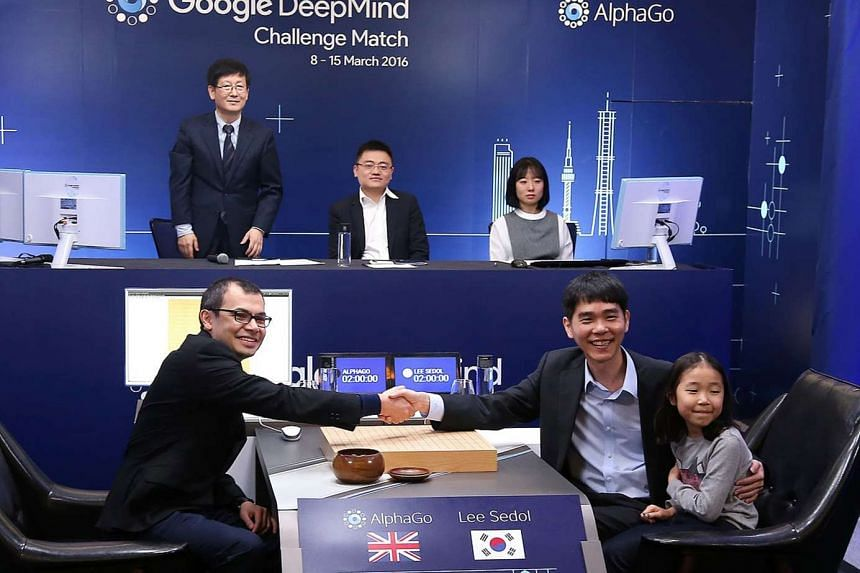 Google Deepmind head Demis Hassabis (left) shaking hands with Mr Lee Se Dol, a legendary South Korean player of Go - a board game widely played for centuries in East Asia - with his daughter in a game room ahead of the Google DeepMind Challenge Match