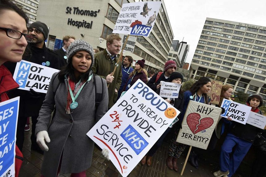 Junior doctors and supporters hold placards during a strike outside St Thomas' Hospital in London on March 9, 2016.