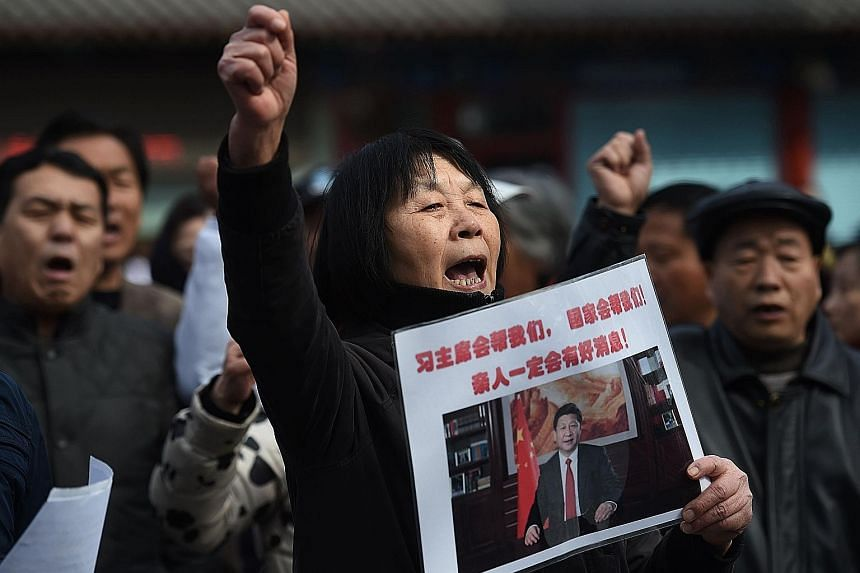 "Ms Dai Shuqin holding a poster that reads ""President Xi will help us. The nation will help us. Good news about our family is sure to come"", as she took part in a protest outside Lama Temple in Beijing yesterday. Relatives of missing passengers on Fli"