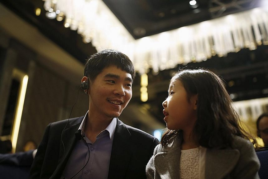 Nine-dan player Lee Se Dol, 32, with his daughter during a news conference in Seoul, South Korea, yesterday.