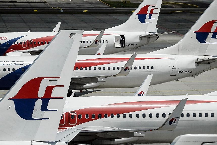 A Malaysia Airlines flight attendant (top) preparing the aircraft prior to departure at Kuala Lumpur International Airport on Feb 25, 2016.