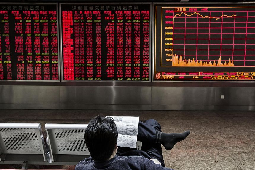 A man reading a newspaper in front of an electronic board displaying share prices at a securities brokerage in Beijing, China, on March 7, 2016.