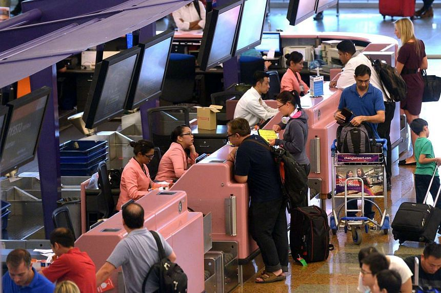 Travellers at a check-in counter in Changi Airport Terminal 2.