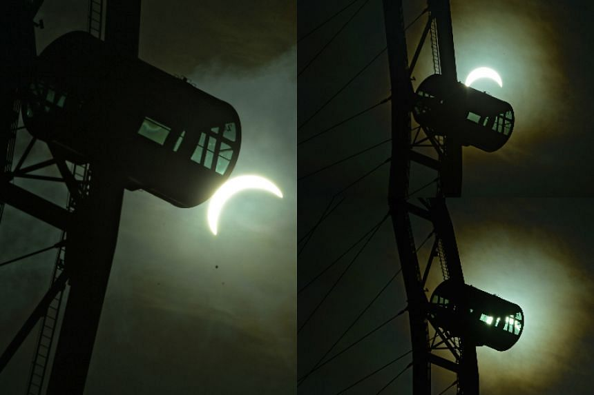 The partial Solar eclipse backdropped against the Singapore Flyer.